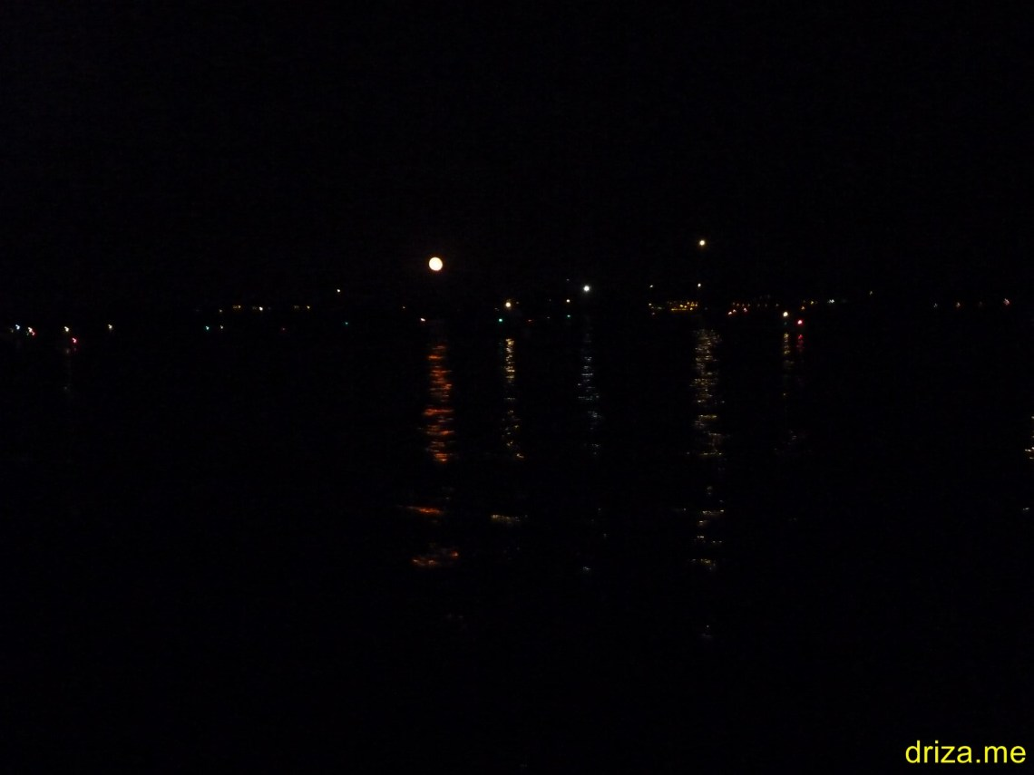 Todas esas luces son barcos saliendo de la bahía. El disco grande en el medio es la Luna